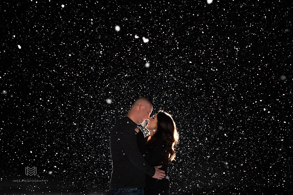 Night engagement session in the snow with couple backlit