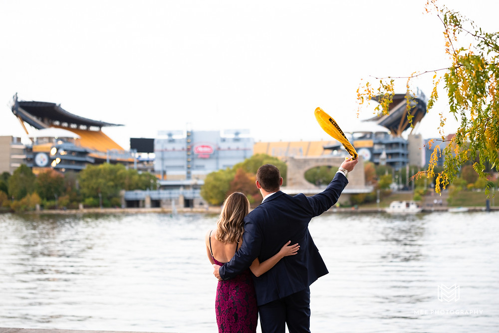 Couple waving the Pittsburgh Steeler's terrible towel with Heinz Field in the background