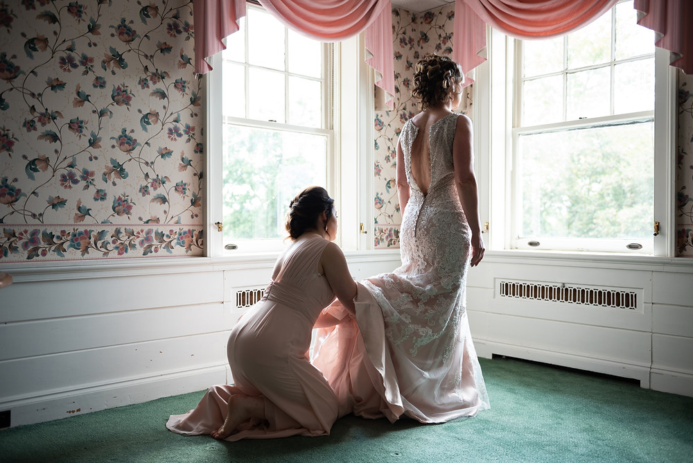 Bride putting on her wedding dress with the help of her bridesmaid at Montour Heights Country club
