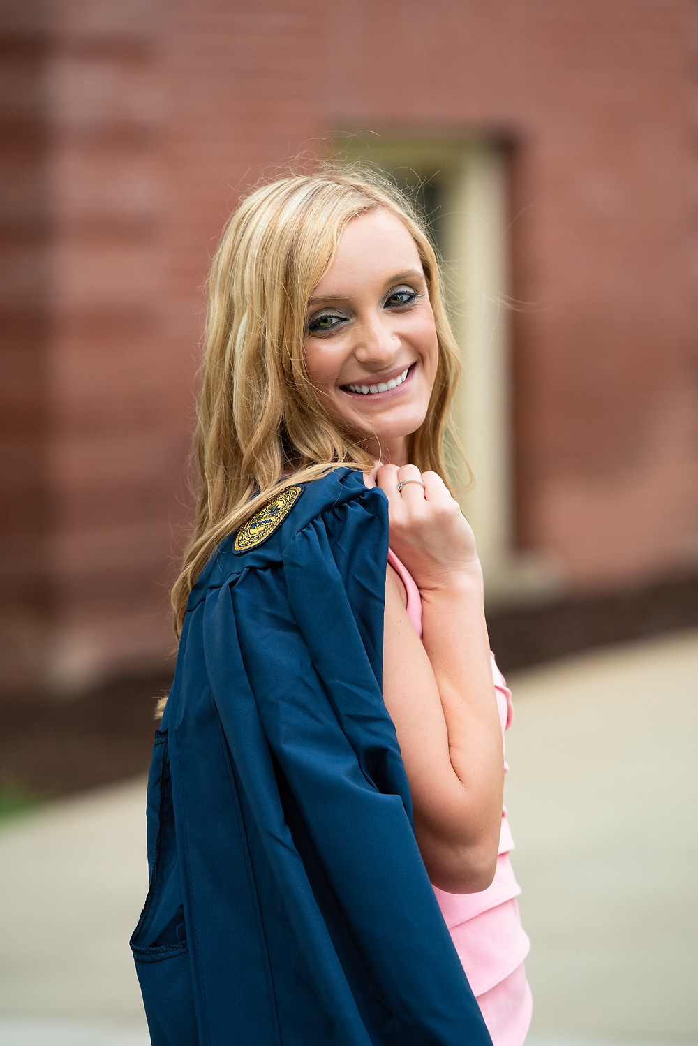 Girl holding blue graduation gown over her shoulder and smiling at the camera in Morgantown, WV