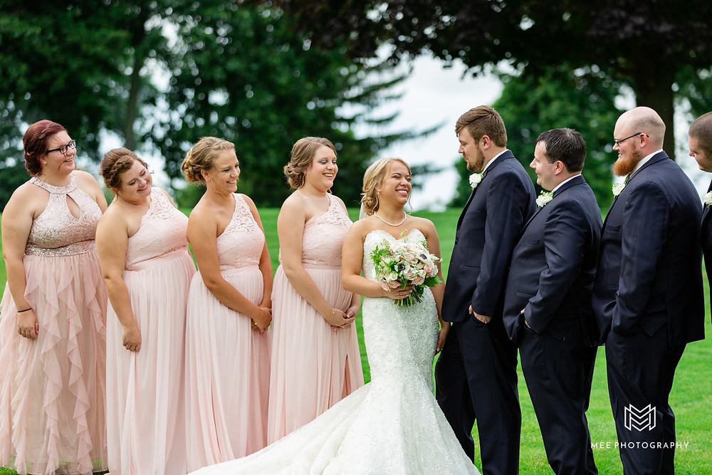 Bridal party laughing during their portraits at the lake club