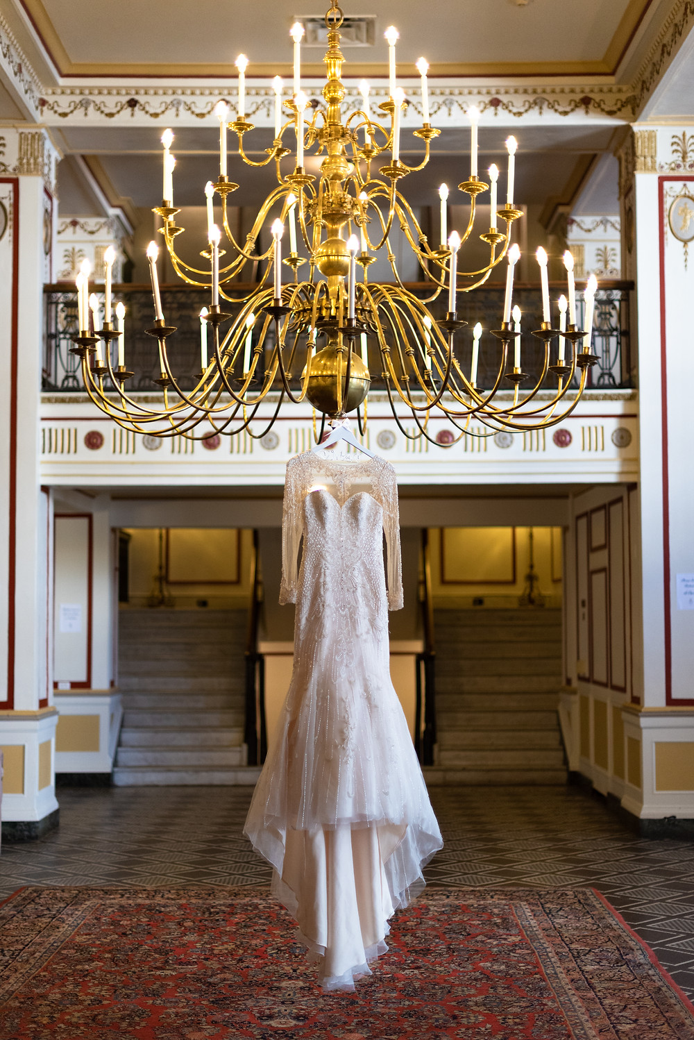 Wedding dress hanging from chandelier at the George Washington Hotel
