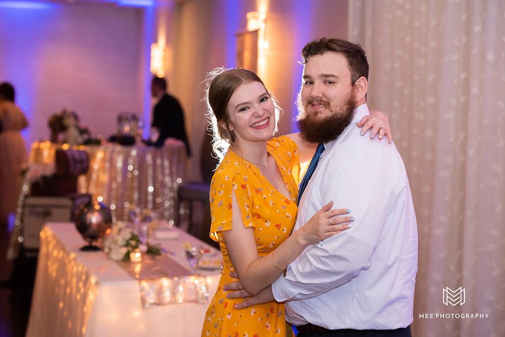 Wedding guests dancing and smiling at the camera