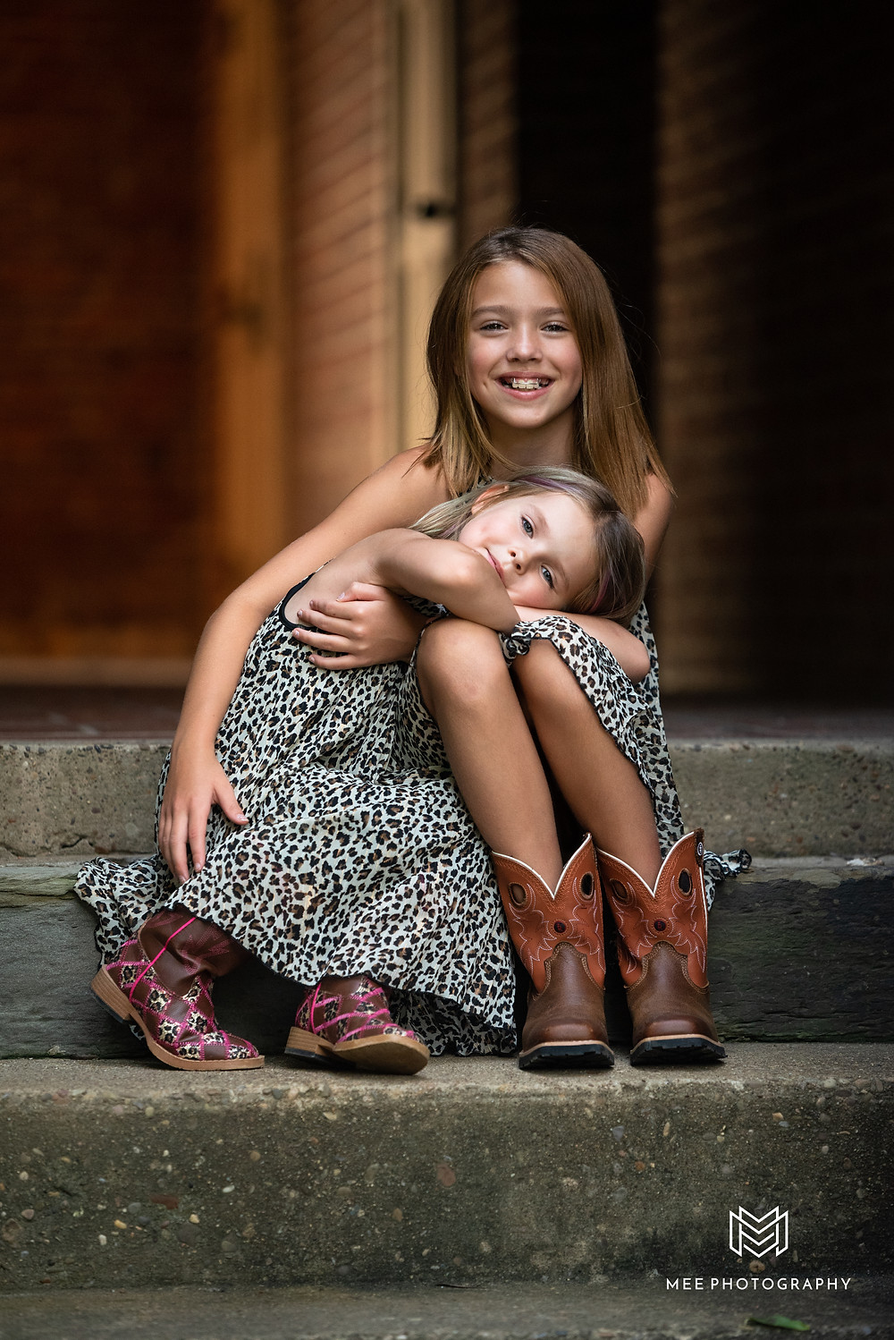 Sisters in leopard print dresses cuddled up on the stairs during their family session
