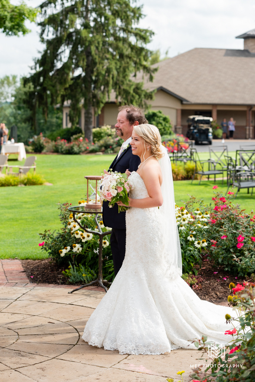 Dad walking daughter down the aisle in a navy tux