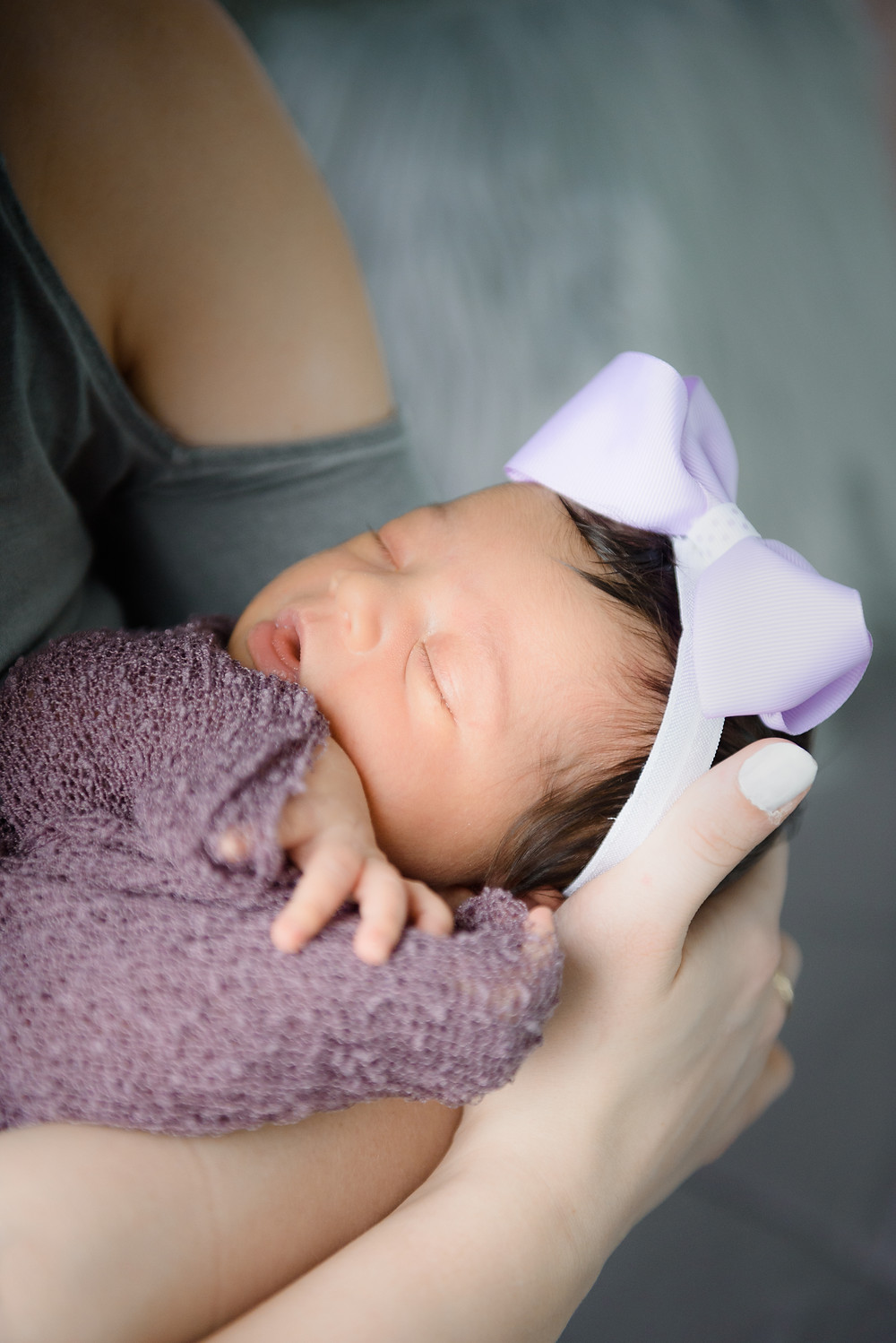 New mom holding her newborn baby girl. Newborn in a purple wrap with a purple bow on her head, sleeping.