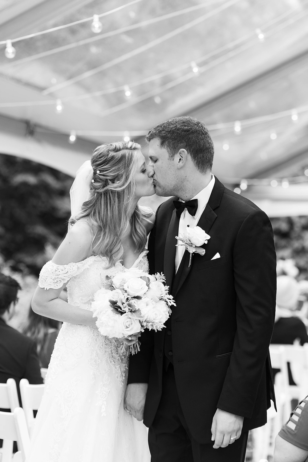 Bride and groom kissing after tented wedding ceremony