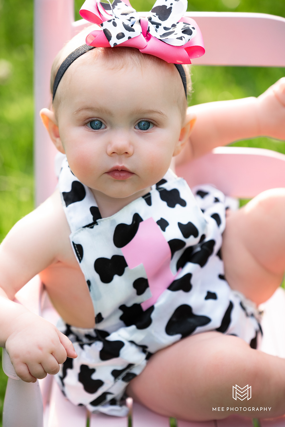 One year old baby girl wearing a black and white cow outfit and sitting in a pink chair