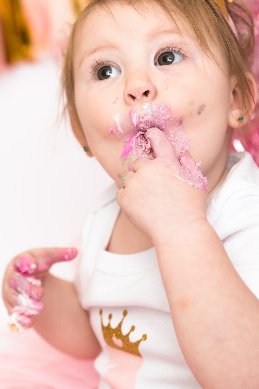 First cake smash session for one year old girl. Her face is covered in frosting.