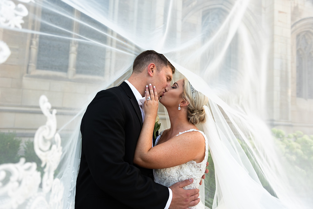 Bride and groom kissing under veil at Heinz Chapel