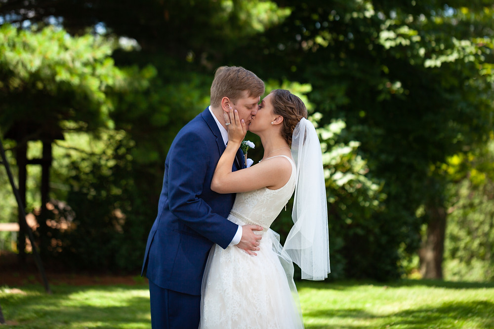 Bride and groom kissing outdoors at Lewis Family Farms during this June wedding