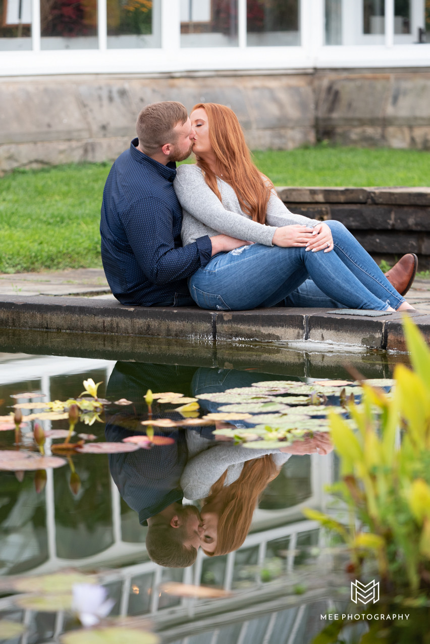 Couple kissing with their reflection on the water at Phipps Conservatory