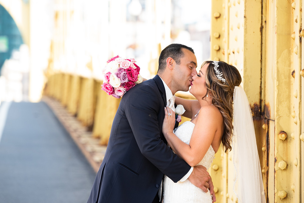 Bride and groom kissing on the Roberto Clemente bridge