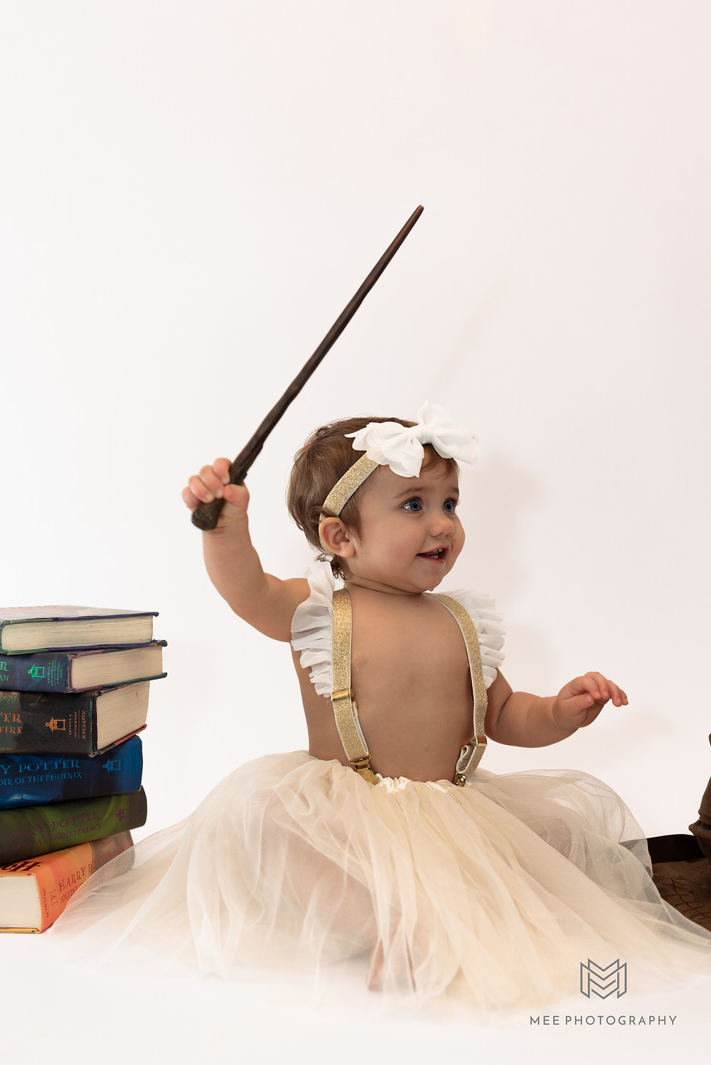 One year old girl waving a wand during her Harry Potter Theme cake smash session