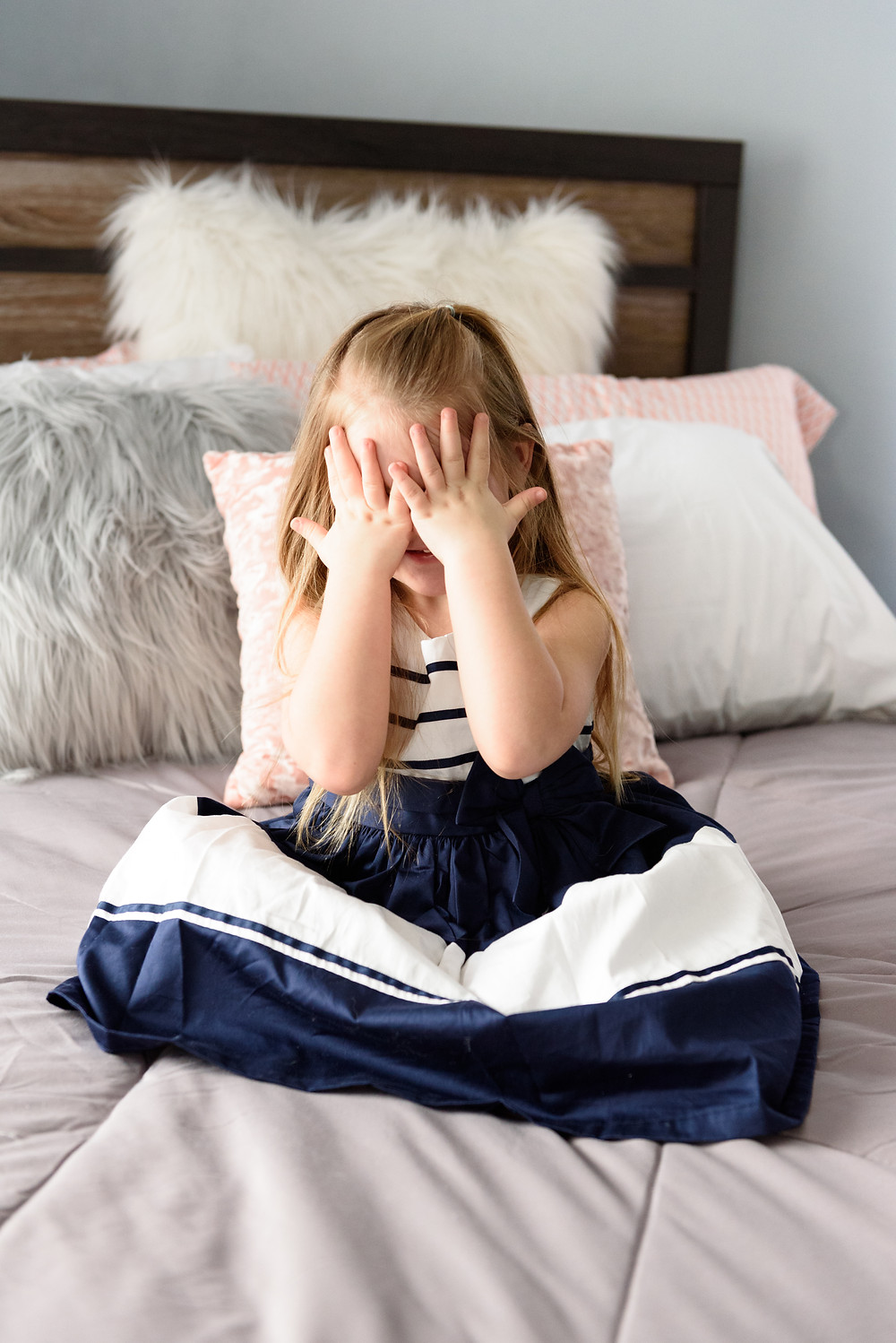 Young girl covering her eyes with her hands while waiting for a surprise.
