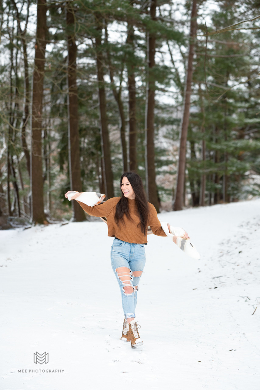 Senior girl in a orange sweater playing with her scarf in the snow