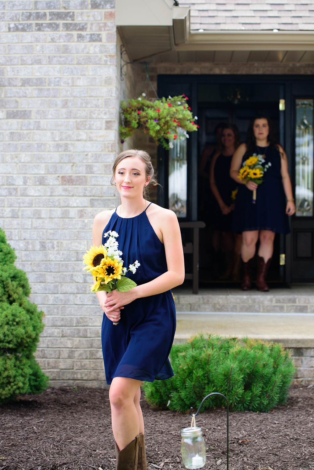 A photography of a bridesmaid walking down the aisle in a navy blue wedding dress and holding sunflowers.