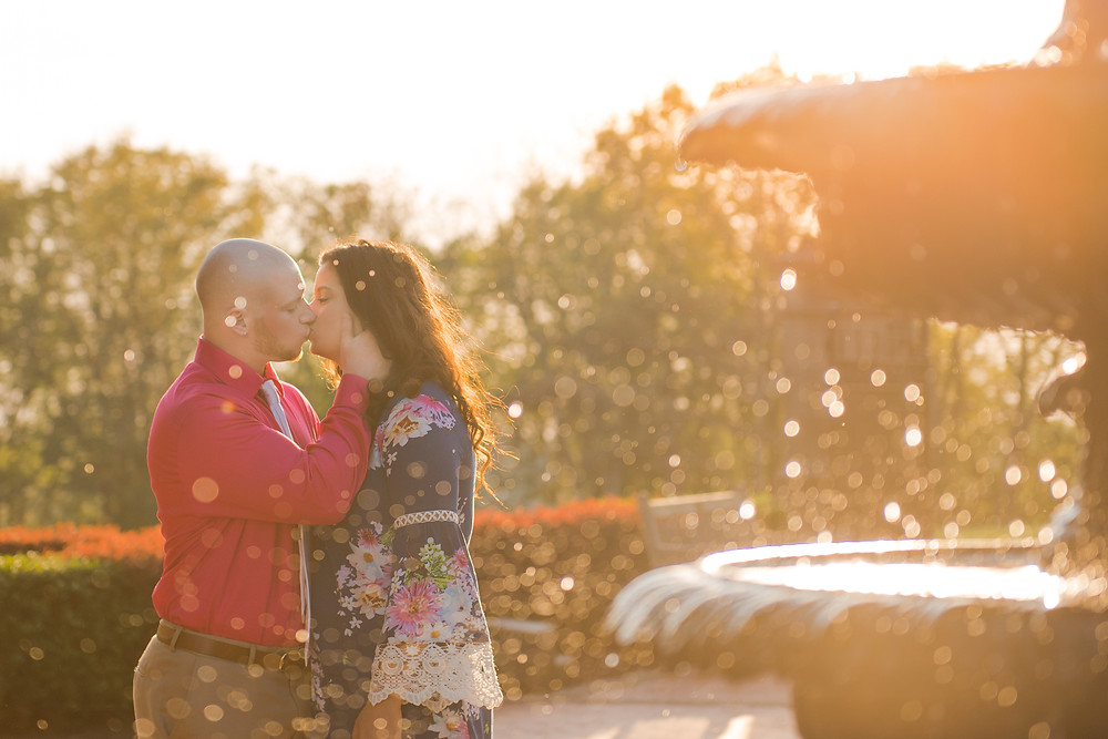 A couple kissing during their engagement shoot behind a fountain. The water droplet are lit by the sunlight.