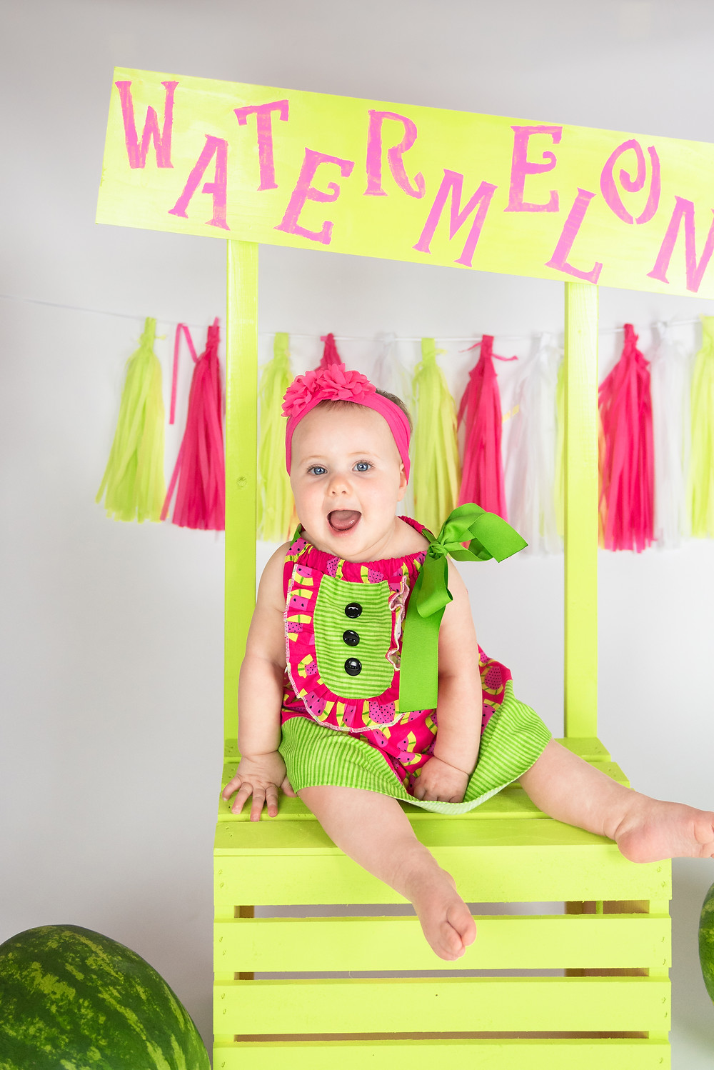 Baby girl laughing during her watermelon themed cake smash photo session.