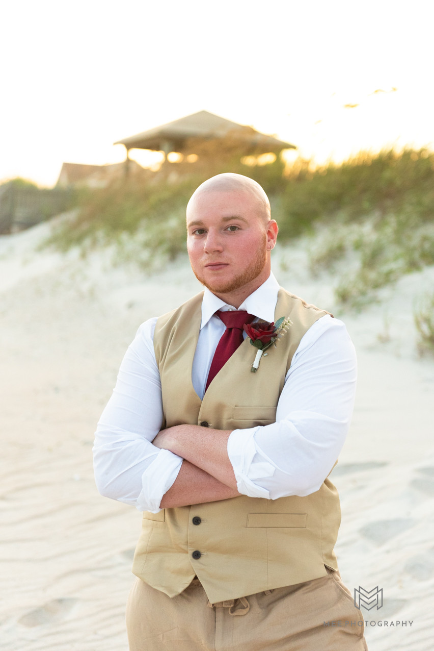 Groom portrait on beach wearing tan tuxedo