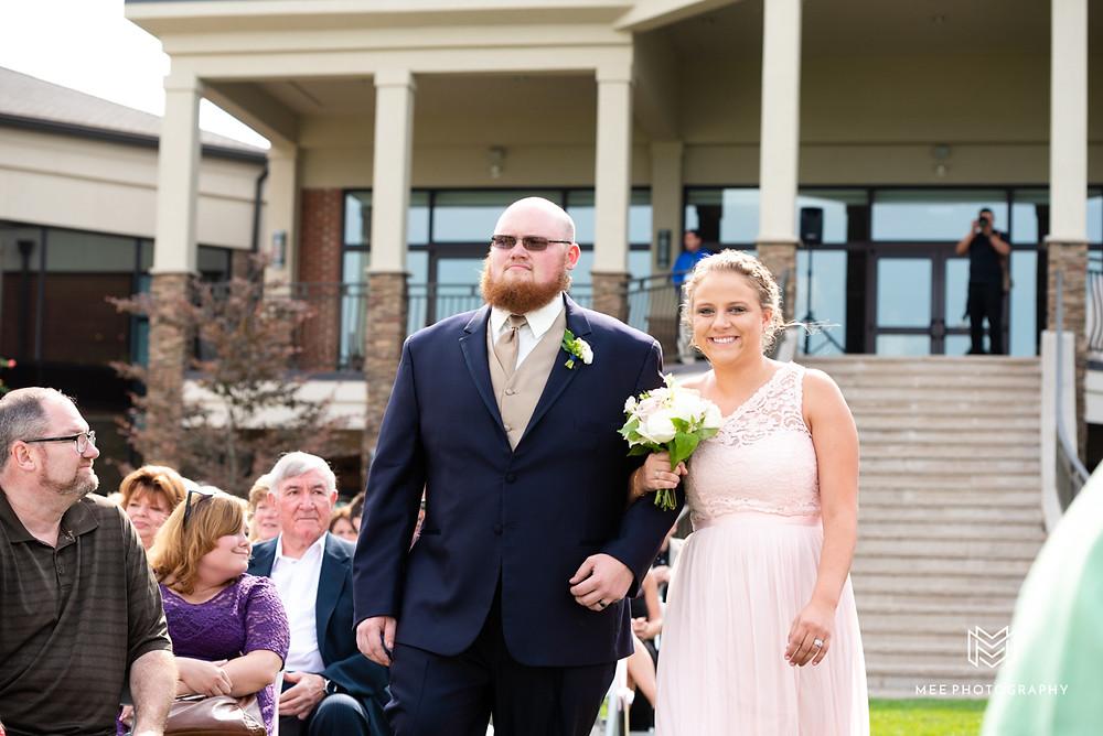 Bridesmaid walking down aisle in a blush dress