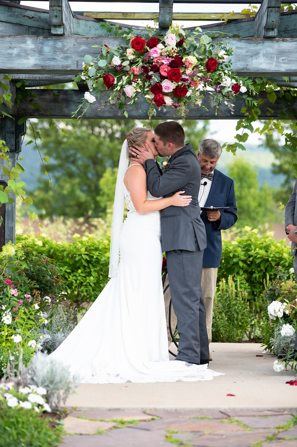 Bride and groom kissing after wedding ceremony under pergola covered in flowers