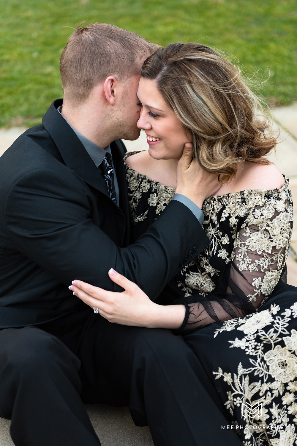 Guy whispering in girl's ear during engagement photos
