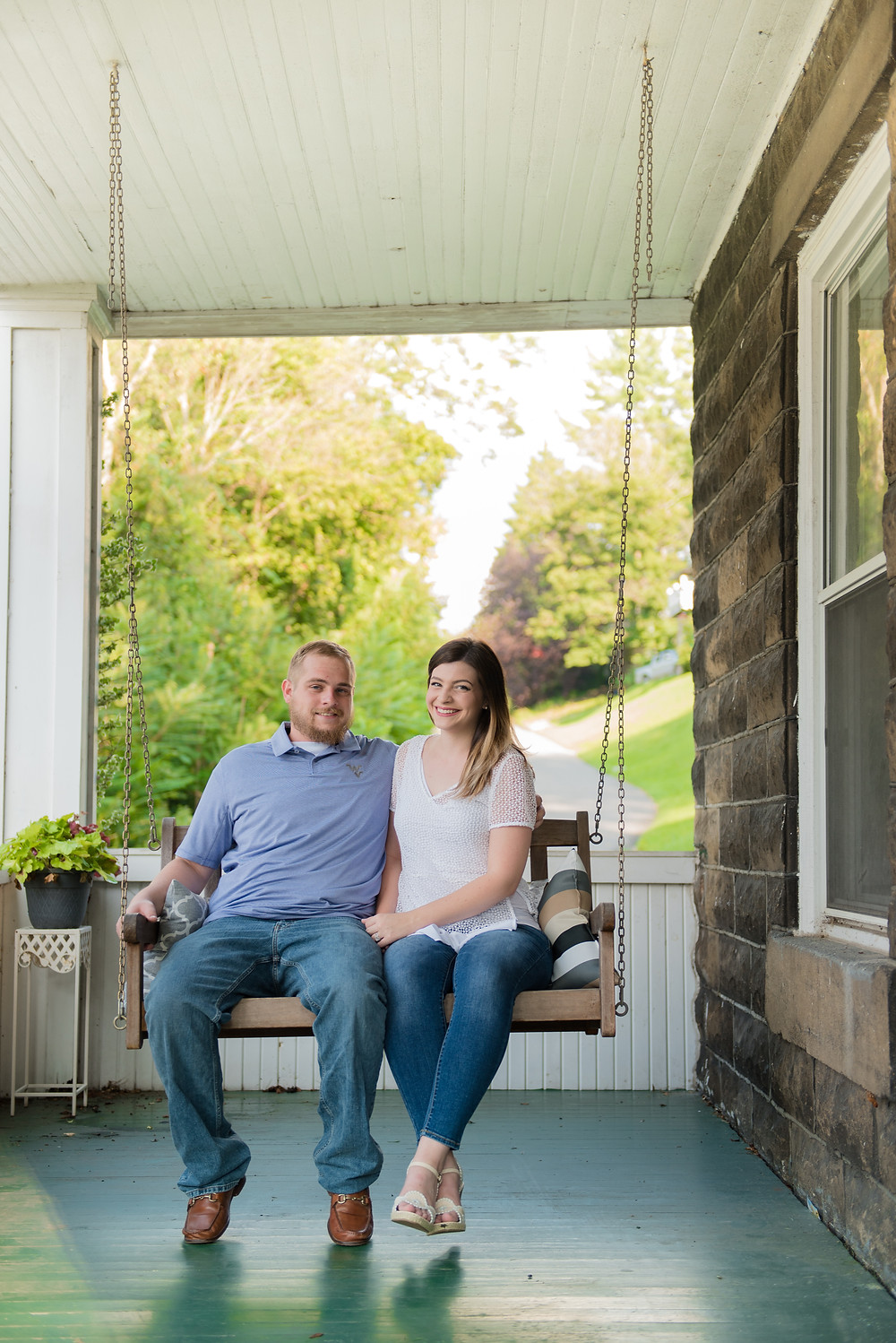 Couple sitting on their porch swing of their new home. They are wearing coordinating colors of blue and white.
