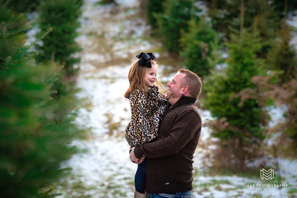 Dad holding daughter in a field of Christmas trees during their photo session.
