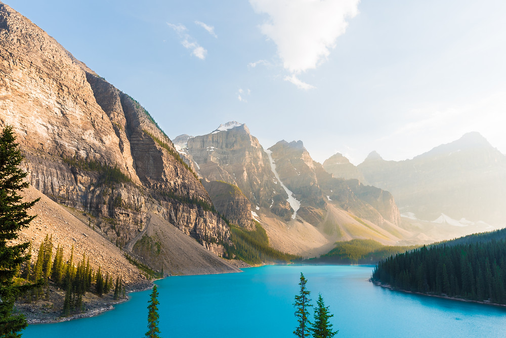 The gorgouse turquoise water of Moraine Lake with the sunset lighting the mountain peaks.