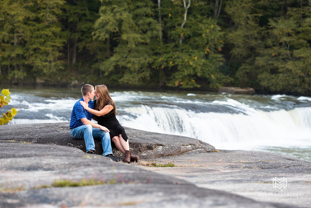 Engagement session with couple posed in front of waterfall at Valley Falls State Park in WV