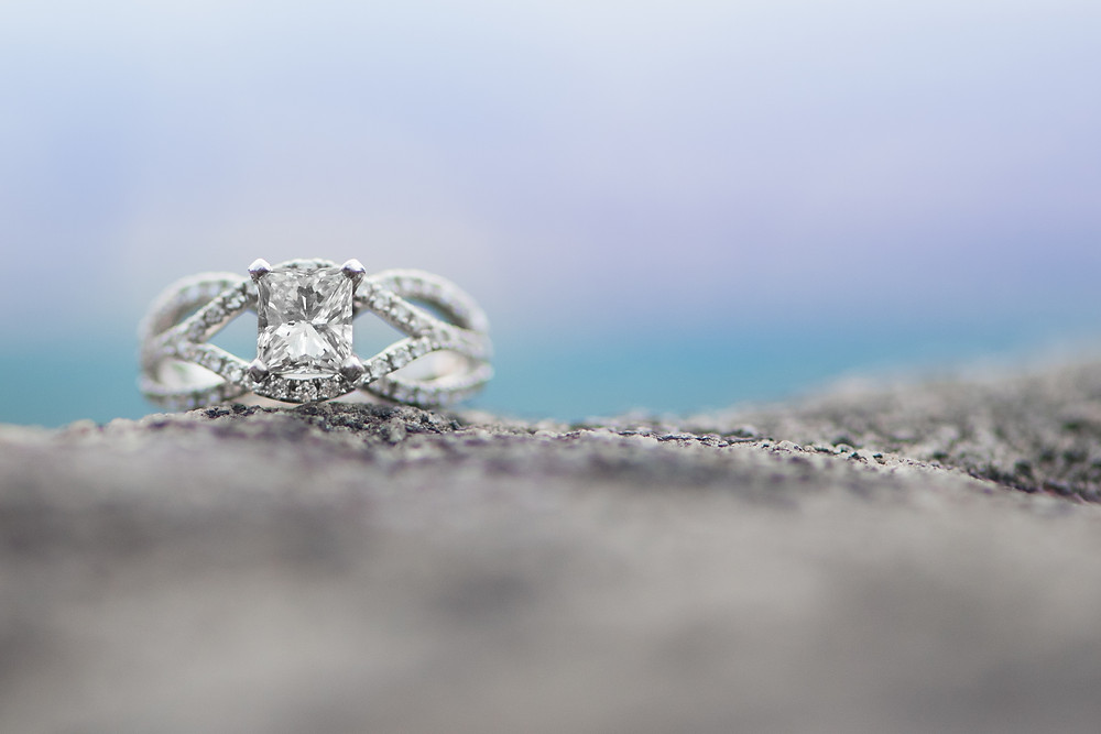 A silver princess cut engagement ring with an intricate diamond band