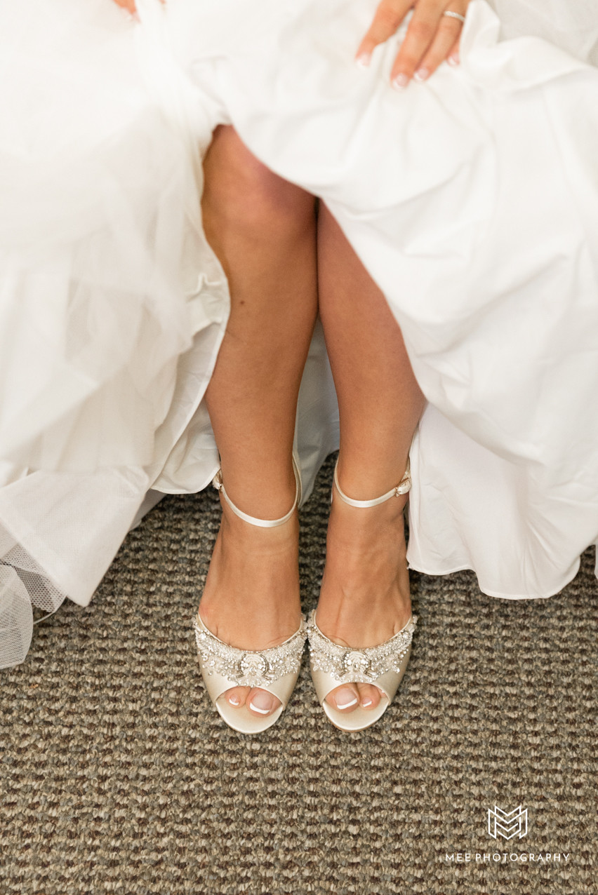 Bride putting on Badgley Mischka shoes