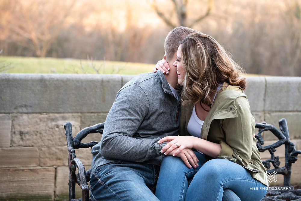 Engaged couple sitting on bench laughing at Hartwood Acres