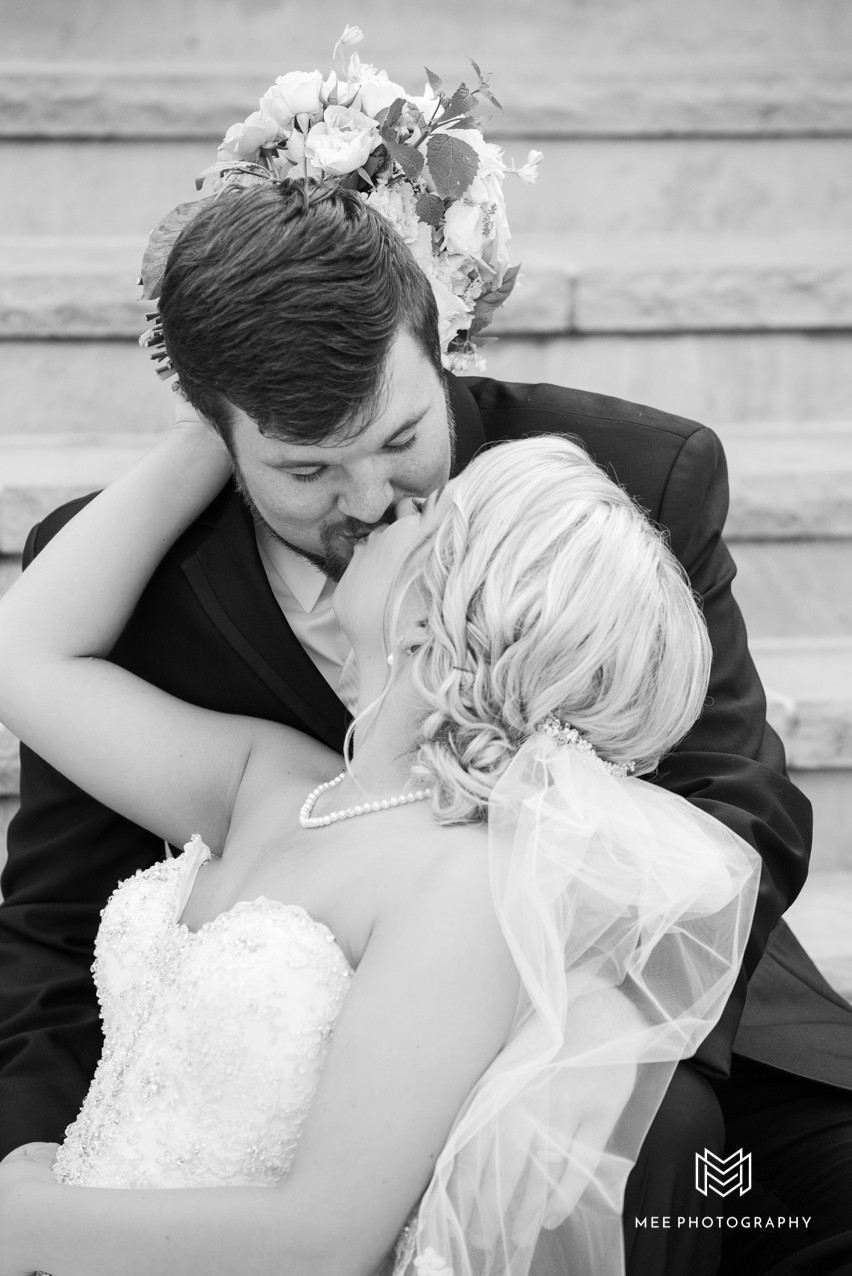 Black and white photo of the bride and groom kissing