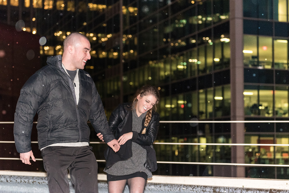 Christmas engagement session at nigh in Pittsburgh. Couple walking while holding hands and laughing