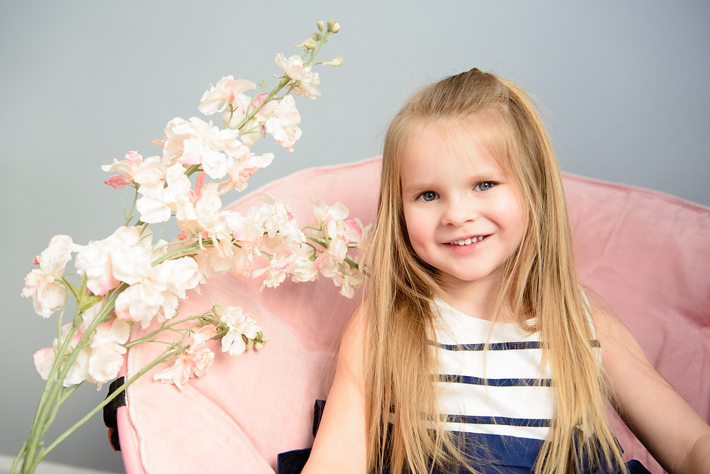 Fourth birthday photoshoot in Weirton, WV. Girl posed sitting on a pink chair.