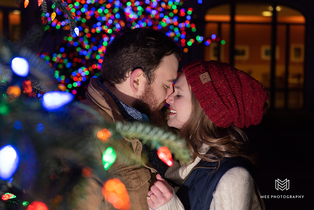 Couple laughing during their Christmas mini session at Phipps surrounded by multicolored lights
