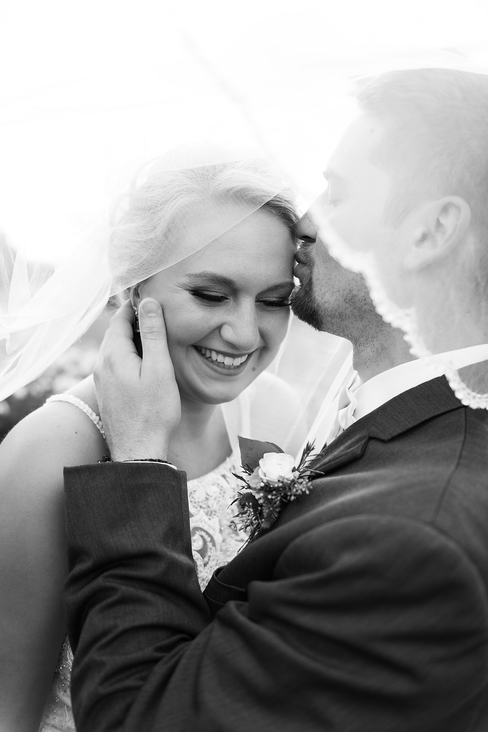 Black and white portrait of the bride and groom under the veil