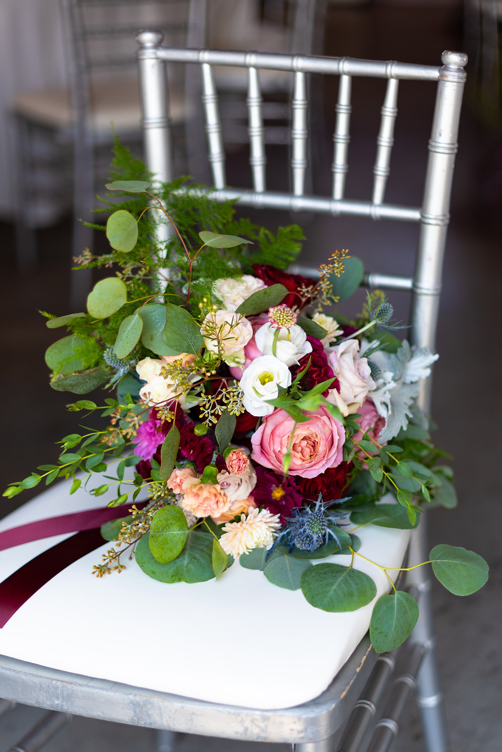 Bridal bouquet by Gypsie Annie with burgundy roses and greenery