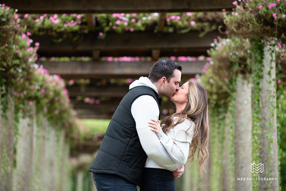 Couple kissing under flower covered pergola at Oglebay Park in WV