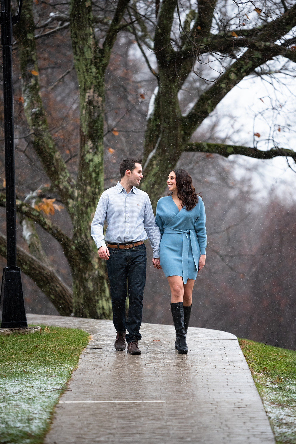 Couple holding hands and walking through the snow during their engagement session at Hartwood Acres