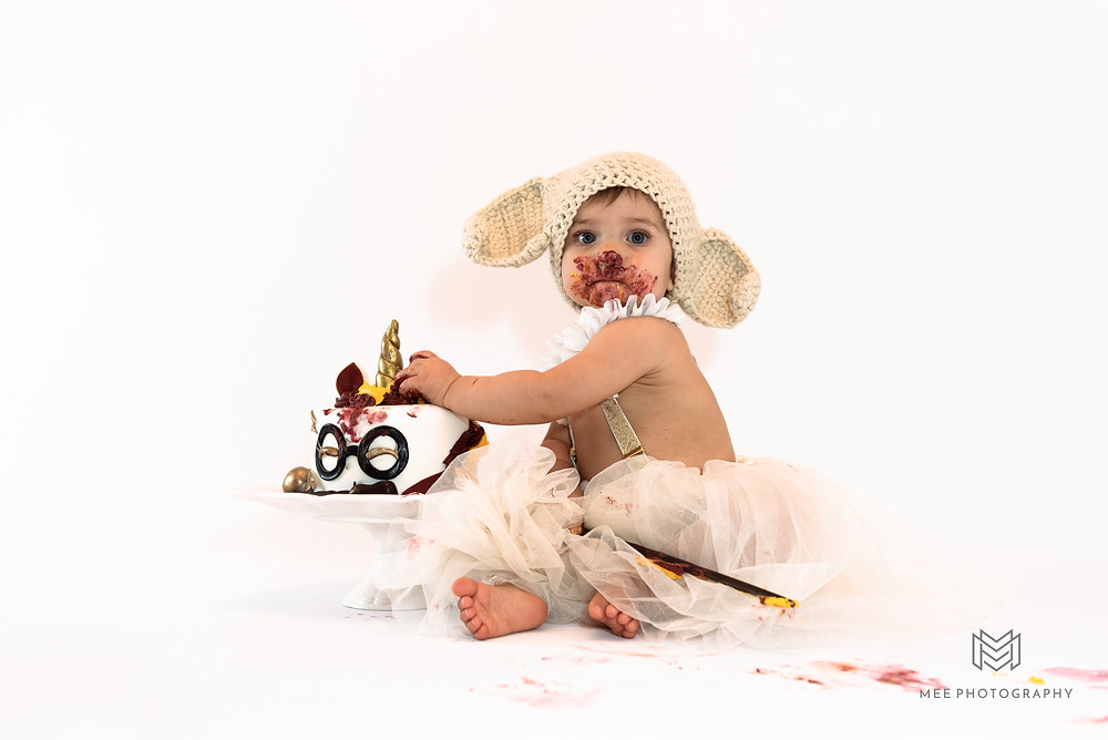 One year old girl covered in cake during her Harry Potter cake smash session
