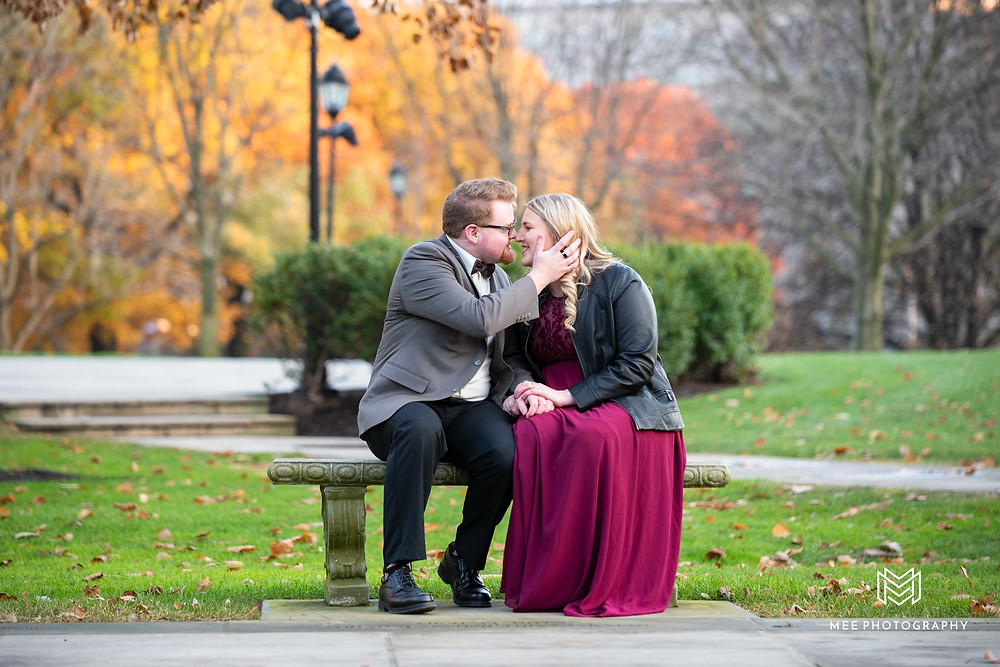 Couple leaning in for a kiss on a bench by Heinz Memorial Chapel; Pittsburgh engagement