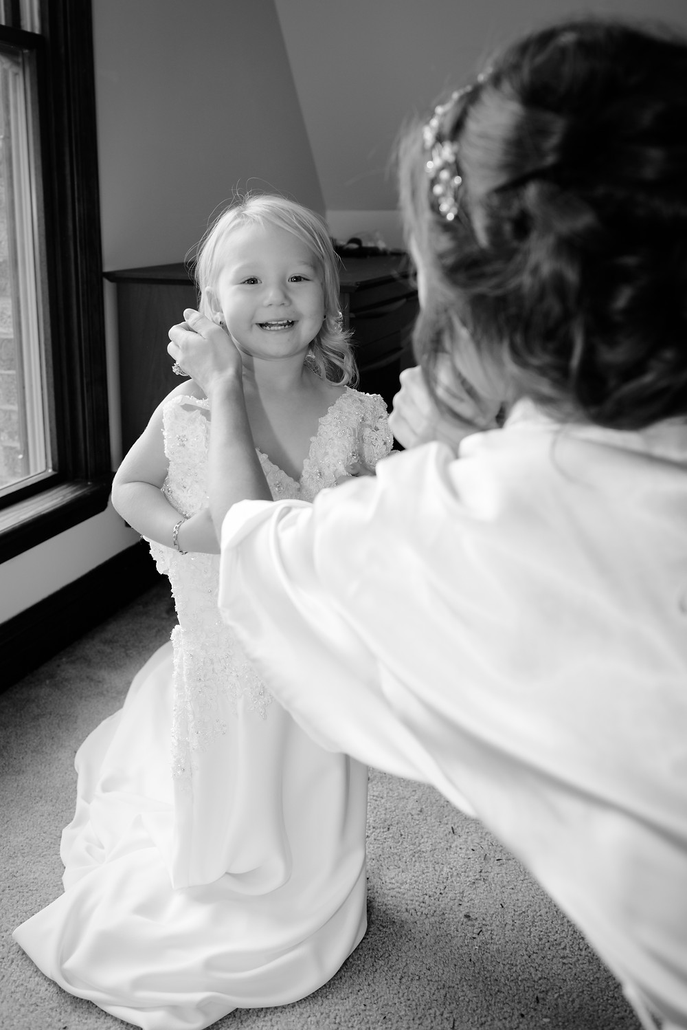 The daughter of the bride trying on her mom's wedding dress.