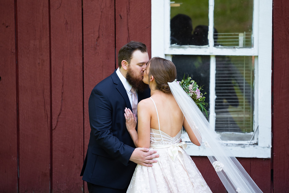 Groom kissing bride during their first look