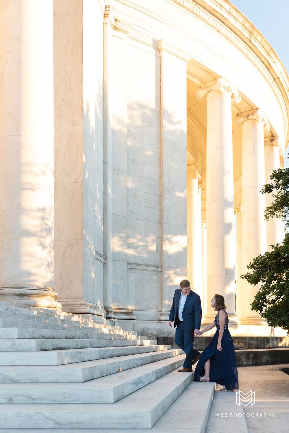 Newly engaged couple walking up the stairs of the Thomas Jefferson Memorial during their engagement session at sunset