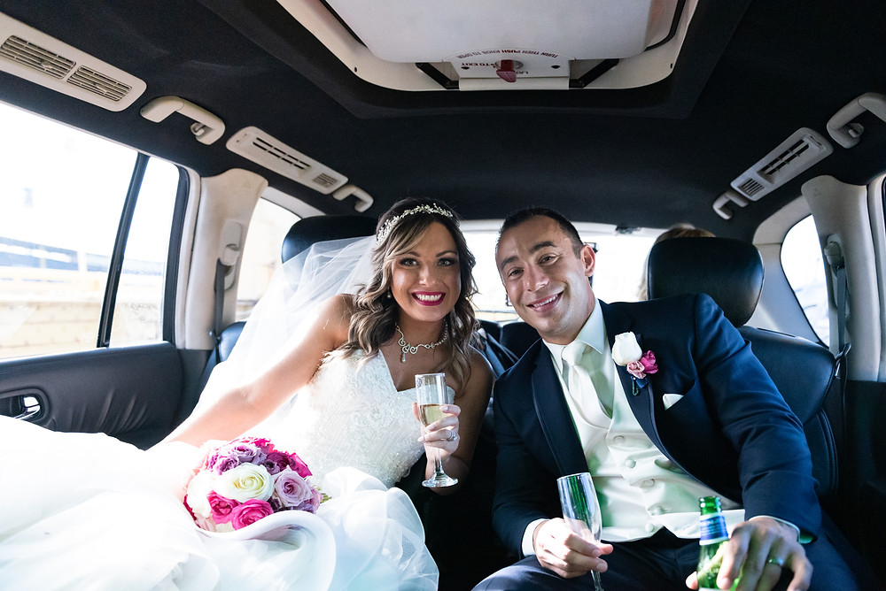 Bride and groom drinking champagne in the limo on the way to the Priory