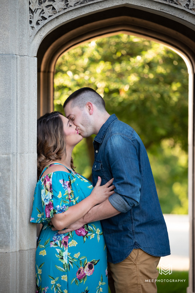 Expecting parents kissing under archway of the Hartwood Acres Mansion in Pennsylvania