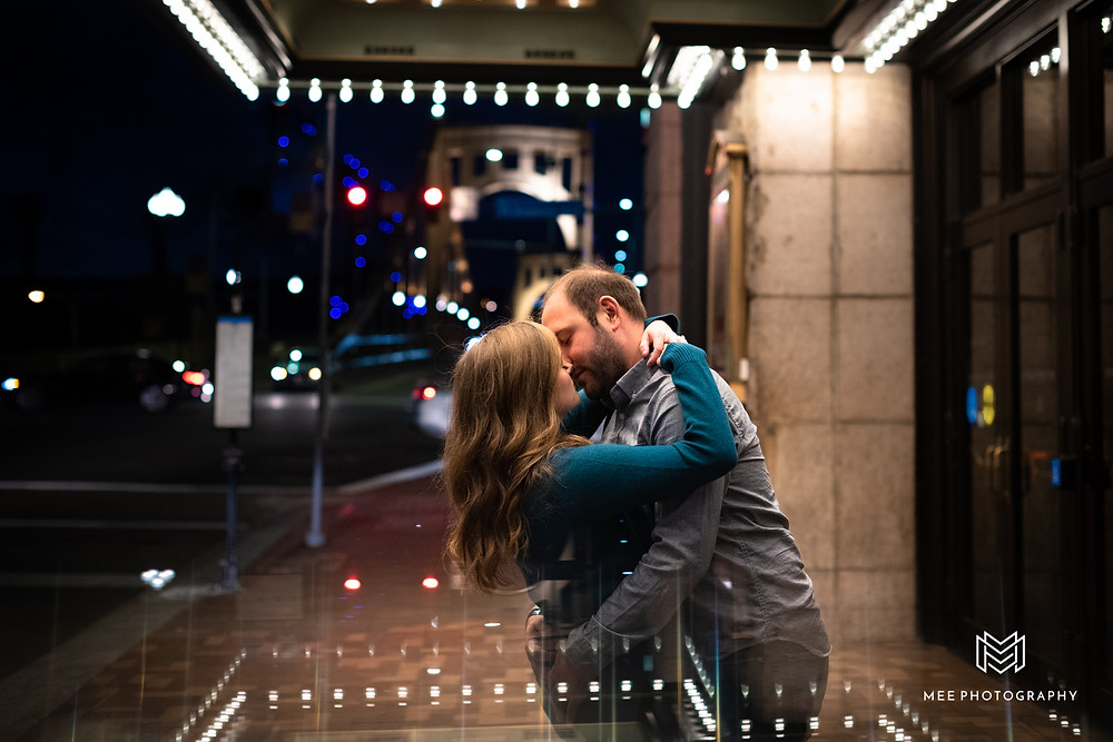 Couple kissing during their engagement session after dark with city lights